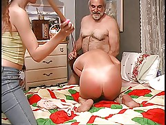 Slut gets down on the bed and guy spanks her hard with wooden paddle